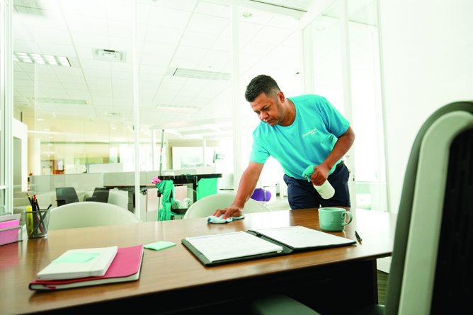 KPC staff in blue uniform cleaning office desk